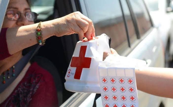 Mujer cooperando desde su vehículo para la colecta de la Cruz Roja