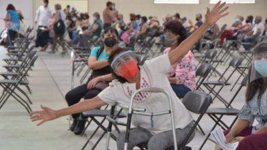 mujer usando muletas, feliz por recibir vacuna contra covid-19 en el Estado de México