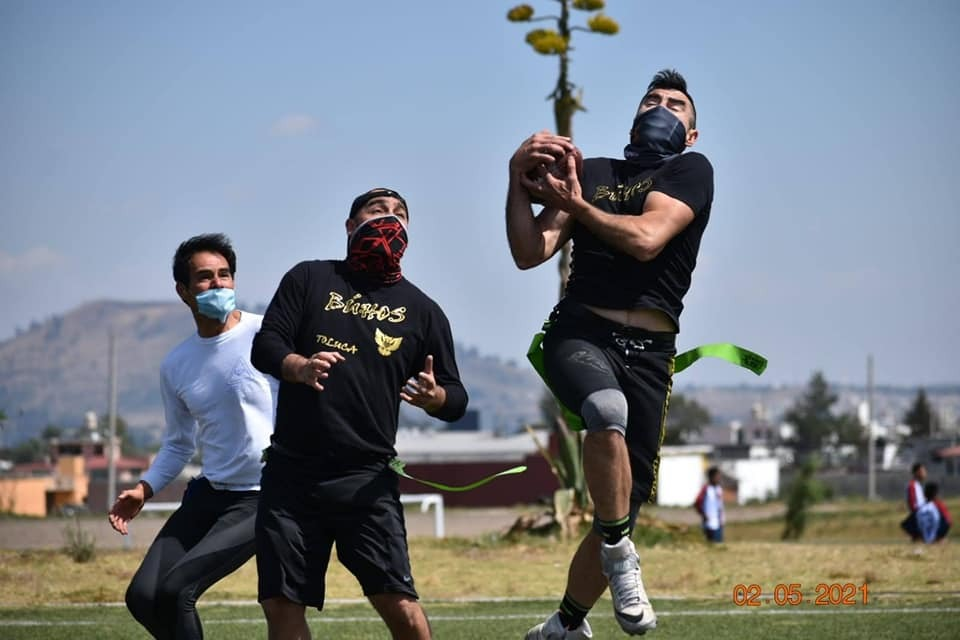 Jugadores de Lobos y Búhos jugando en campo, partido de fútbol americano